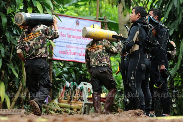 Rescuers carry air tanks to support the search for 12 boys and their football coach trapped for almost ten days in Tham Luang cave in Mae Sai district, Chiang Rai, on Monday. (Photo by Wichan Charoenkiatpakul)