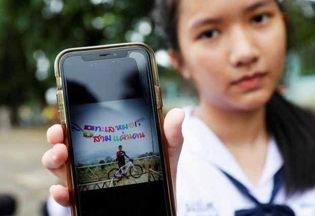 A student shows a photo of her classmate Prachak Sutham, 13, who is a member of an under-16 soccer team that went missing with their coach at a flooded cave, in Mae Sai Prasitsart school, Chiang Rai, Thailand, on Monday. (Reuters photo)