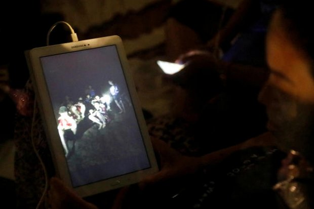 A mother looks at video of her son and other boys of the Under-16 Wild Boar football team, found late Monday at the Tham Luang cave complex in Chiang Rai's Mae Sai district. (Reuters photo)
