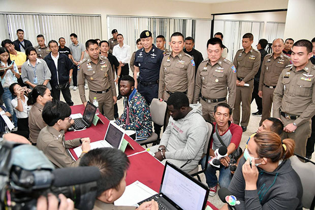 Romance scammers Rogers Kyeyune, 31, Emmanuel Kasoma, 37, from Uganda, and Thai woman Wilaiwan Phetthong, 24,far right, during a press briefing at police headquarters on Wednesday following their arrest on Koh Samui in Surat Thani. (Photo by Tourist Police Bureau)