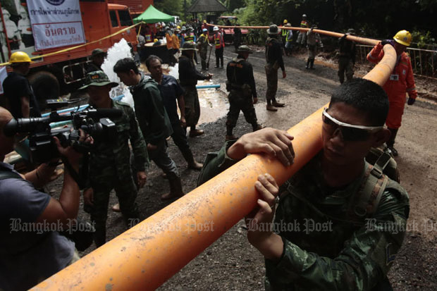 Workers extend the duct that supplies air to rescuers inside Tham Luang cave in Chiang Rai's Mae Sai district, as the operation the bring out the 13 footballers continues. (Photo by Patipat Janthong)