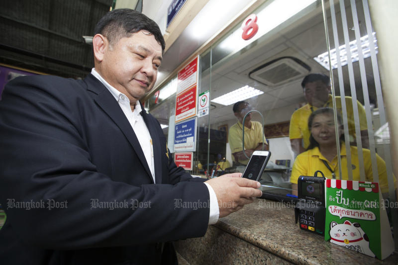 Deputy governor of the State Railway of Thailand Voravuth Mala buys a ticket using a mobile phone and QR code at Hua Lamphong station on Thursday. (Photo by Pawat Laopaisarntaksin)