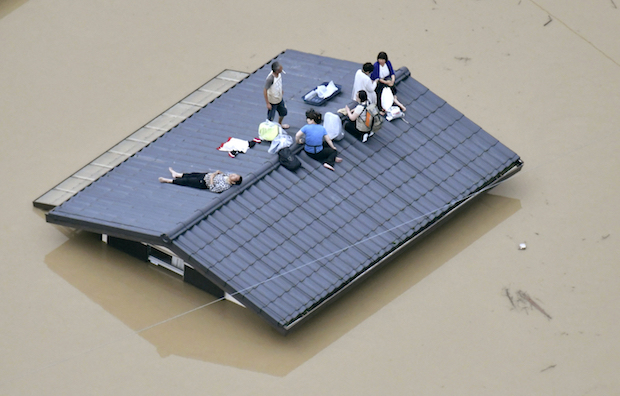 People wait to be rescued on the roof of a house almost submerged in floodwaters caused by heavy rains in Kurashiki, Okayama prefecture, southwestern Japan on Saturday. (AP Photo)