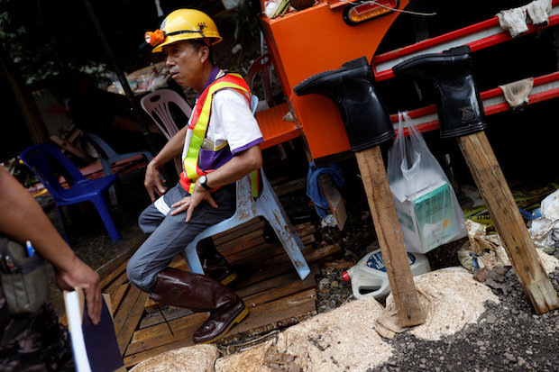 A worker takes a break during the pumping operation at the Tham Luang cave complex in Chiang Rai on Saturday afternoon. (Reuters Photo)