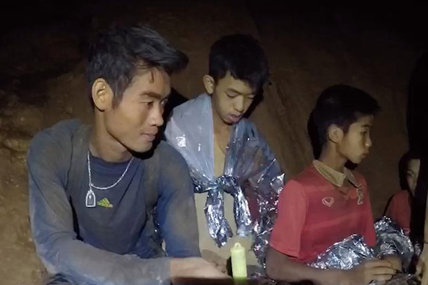 Coach Ekkapol Chantawong with some of the young footballers in Tham Luang cave after divers found them on July 2. (Thai Navy Seal photo)
