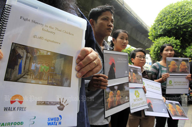 Representatives of 14 workers hold anti-slavery posters during a protest against Thammakaset Farm, on Silom Road, Bangkok on Sept 2, 2016. (Photo by Apichart Jinakul)