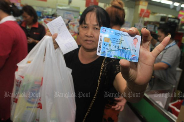 Low-income earners show their state welfare cards while shopping for food and other necessities. (File photo by Somchai Poomlard)