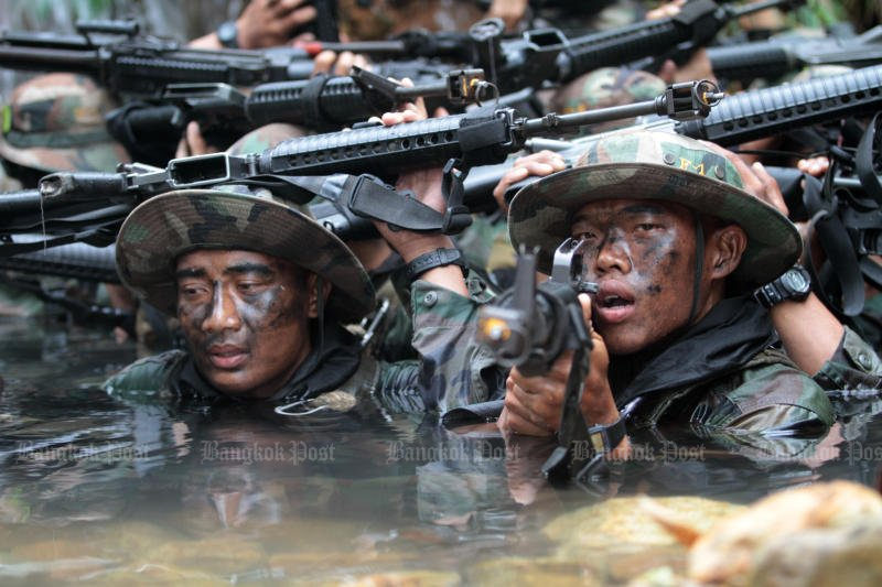 Seals of the navy's Underwater Demolition Team struggle through a muddy training course during the annual 120-hour Hell Week at the conclusion of their one-year brutal basic training. Cave diving is about to be added to the schedule. (File photo by Jetjaras na Ranong)