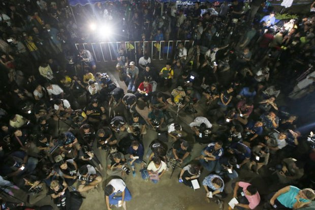 Journalists were penned up (reporters seated on the ground, foreground, cameras to their rear) four kilometres from the cave entrance and were given 'approved' information at briefings like the above by mission coordinator Narongsak Osotthanakorn. (AP photo)