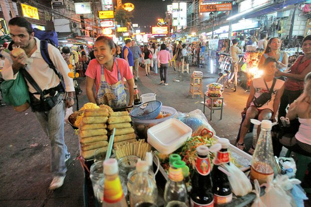 A food vendor navigates through traffic and pedestrians on Khao San Road. City Hall has ordered pavement vendors to move out by Aug 1. (AP file photo)