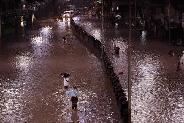 Filipinos wade through a flooded street in Las Pinas city, south of Manila, on Tuesday after tropical storm Son-Tinh passed through the north of Luzon island. (Photo by EPA)