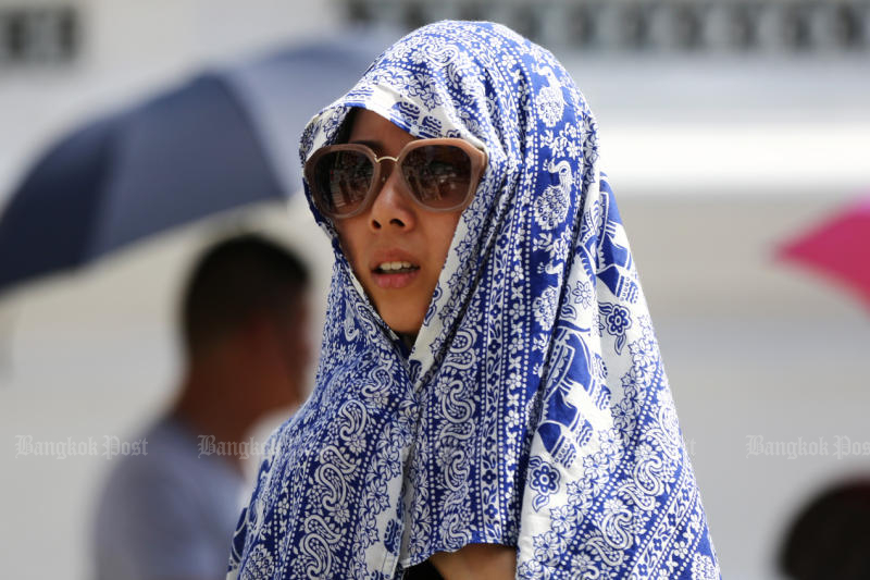 A Chinese tourist shields her head from the sun with a scarf during a visit to the Temple of the Emerald Buddha. (Post Today photo)