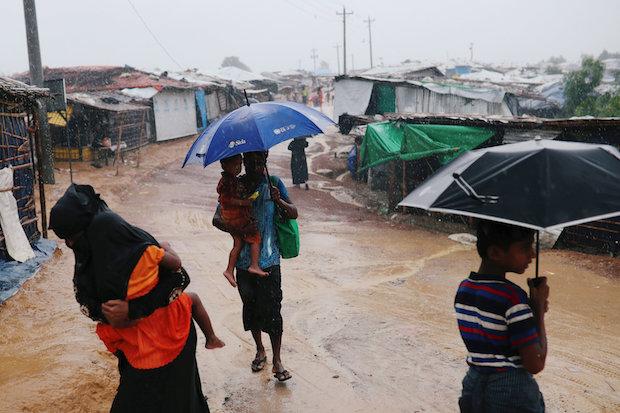 Rohingya refugees walk through heavy rain at the Kutupalong camp inCox'sBazar, Bangladesh. (Reuters Photo)