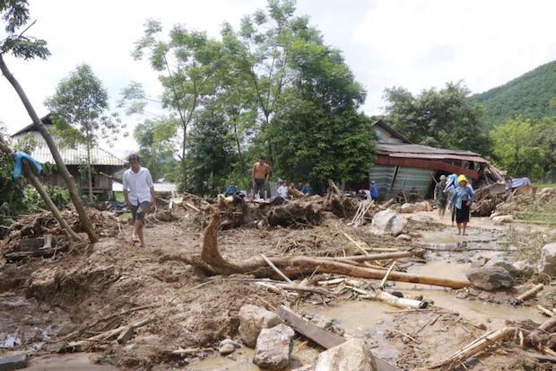 People clear debris in a village damaged by flash floods in Yen Bai, Vietnam, on Saturday. (EPA photo)