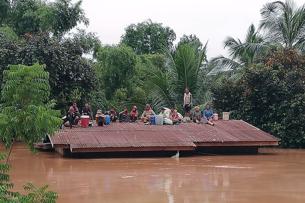 Lao villagers are stranded on a roof of a house after the Xe Pian Xe Nam Noy dam collapsed in a village near Attapeu province, Laos, on Tuesday. (EPA-EFE/ABC Laos News)