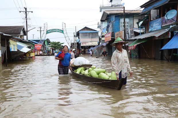Residents use a boat to transport goods through floodwaters on a street in Hpa-an, the capital of Karen state, on Friday. (AFP Photo)