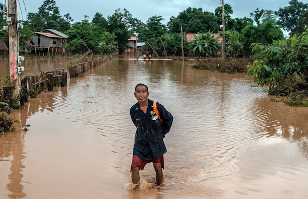 A man wades through floodwaters in Khom Kong, Laos. (New York Times Photo)