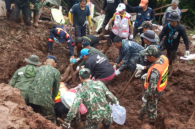 Soldiers and rescuers search for people trapped by a mudslide that hit a village in Bo Klue district of Nan on Saturday morning. Eight bodies were recovered, all from one family. (Photo by Rarinthorn Petcharoen)