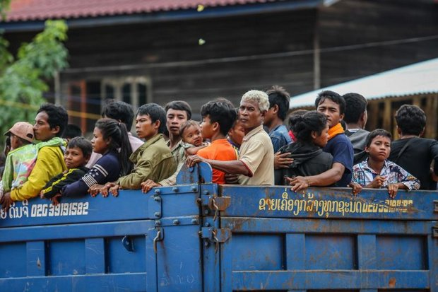 Survivors of the dam collapsed are trucked through an Attapeu province village. Rescuers and relief workers are battling thick mud and floodwaters that refuse to drain to find, feed and house survivors of the disaster. (AFP photo)