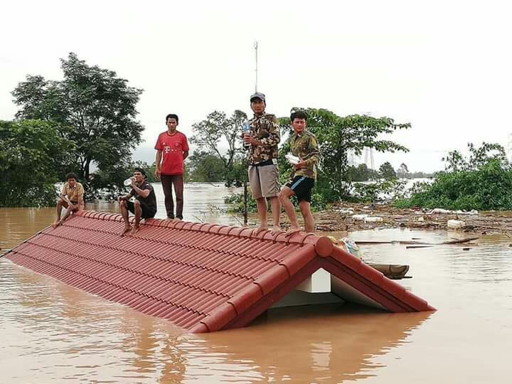 Lucky survivors of the Laos dam collapse perch on the roof of a house while waiting for rescue. (FB/THOLAKHONG Khmu)