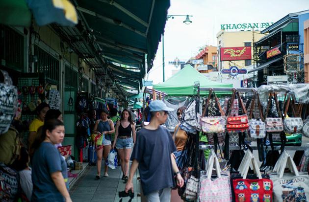 Tourists walk past street vendor shops on Khao San road on Wednesday. (Reuters photo)
