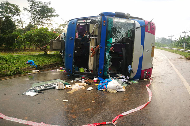 A bus bound for Phuket is seen on its side in Khirirat Nikhom district in Surat Thani province on Sunday. (Photo by Supapong Chaolan)
