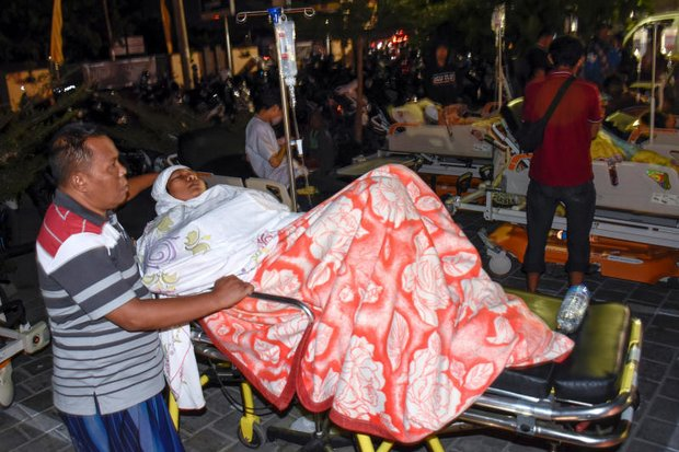 An injured woman waits alongside patients who were moved out of the Mataram City hospital into the street after the earthquake struck. (Antara Foto via Reuters)