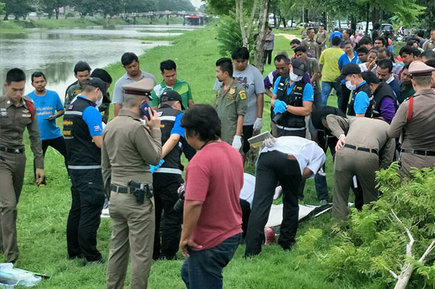 A crowd gathers to watch as police examine the body of the man found dead in Khlong Rangsit canal in Thanya Buri district, Pathum Thani, on Wednesday morning. (Photo taken from @ejan2016 Facebook page)