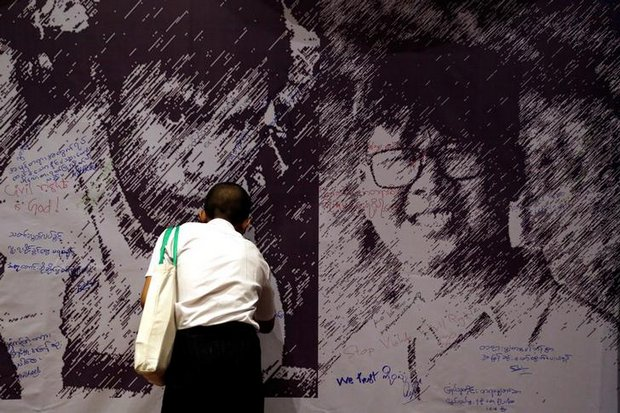 A man signs a large poster in Yangon showing the jailed journalists Wa Lone (right) and Kyaw Soe Oo. (Reuters photos)