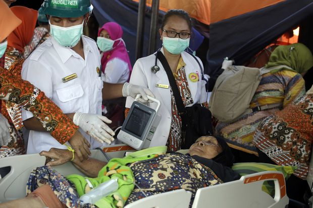 A woman injured in an earthquake is treated in Mataram, Lombok, on Thursday. The Indonesian island of Lombok was shaken by a third big earthquake in little more than a week Thursday. (AP Photo/Firdia Lisnawati)