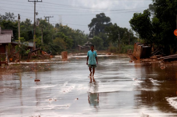 A man walks through his village in Attapeu province as floodwaters from the collapsed Xe-Pian Xe-Namnoy dam lowly recede. (Reuters photo)