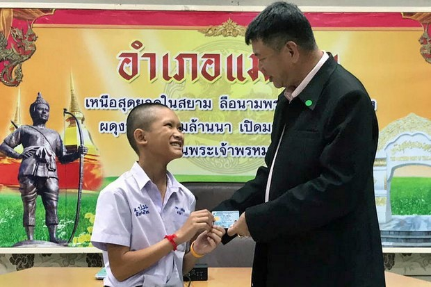 Mongkol Boonpiam, left, one of the four Wild Boars football team members who have officially received Thai nationality, smiles as he receives his citizen's ID card from Mae Sai District Chief Somsak Kanakham on Wednesday. (Photo by Chiang Rai Public Relations Office via EPA)