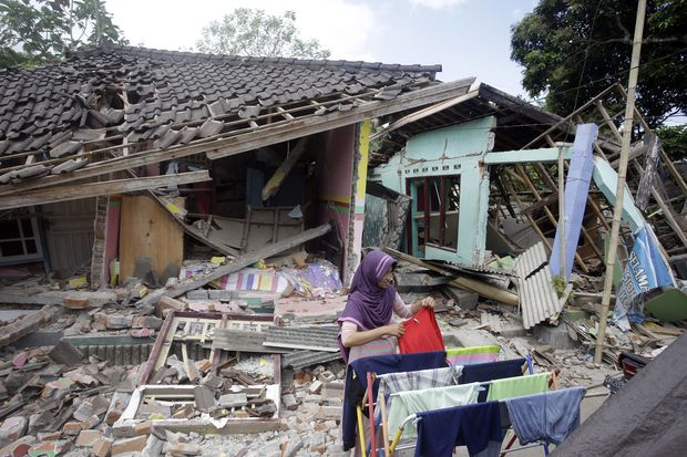 A woman dries her laundry in front of her home destroyed by Sunday's earthquake in West Lombok. (AP photo)