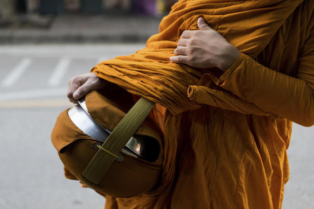 A monk carries his food container during daily almsgiving, in Bangkok, July 4, 2018. (Amanda Mustard/The New York Times)