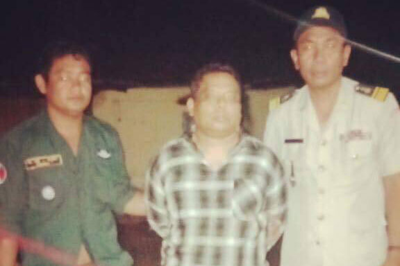 Murder suspect Panya Yingdung, centre, is arrested by Cambodian officials Wednesday night. (Police photo)