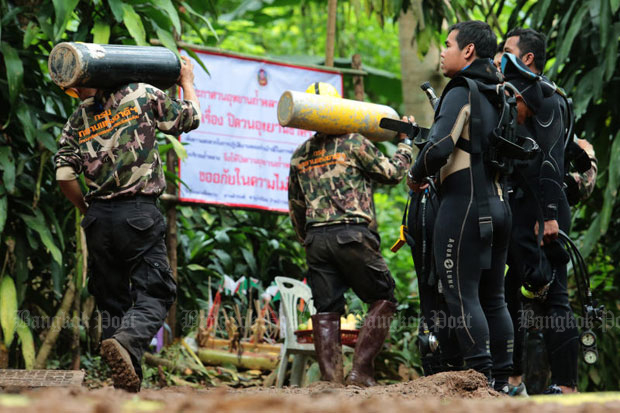 Divers watch spare air tanks being carried into Tham Luang cave in Chiang Rai during the operation to save the 12 boys and their football coach in early July. (Photo by Wichan Charoenkiatpakul)