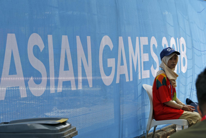 A volunteer waits outside a venue as final preparations are made at the 18th Asian Games in Jakarta on Friday. (AP photo)