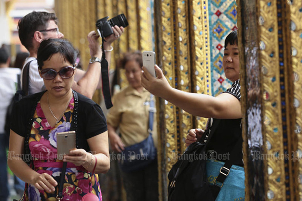 Chinese tourists visit the Temple of the Emerald Buddha, one of their favourite destinations in Bangkok. (Photo by Patipat Janthong)