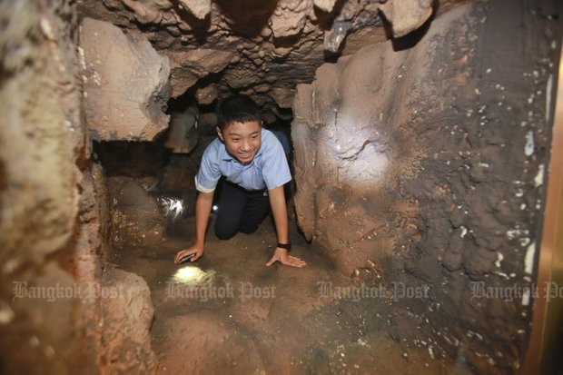 A schoolboy crawls through a recreation of the Tham Luang caves, currently on show at a Ministry of Culture exhibition. (Photos by Somchai Poomlard)