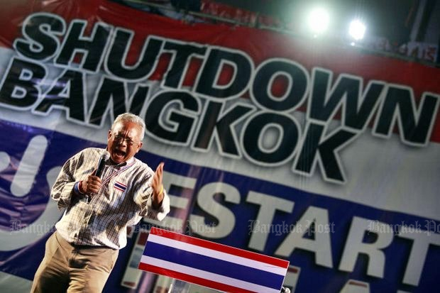 Suthep 'Kamnan' Thaugsuban harangues a crowd during Bangkok Shutdown just before the 2014 coup. Economists claim 20 years of unbroken political division have cost the country 0.4% growth every year. (File photo)