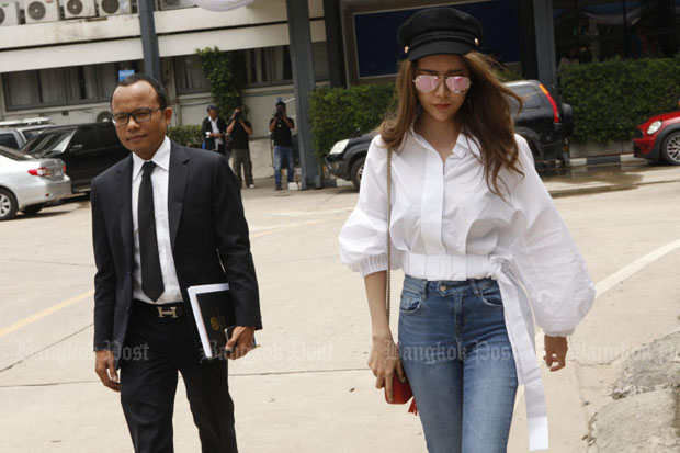 Kanthana Siwathanapol, 28, (right) with her lawyer Seksan Trachu, at the Crime Suppression Division in Bangkok to answer a charge of money laundering on Tuesday. (Photo by Pornprom Satrabhaya)