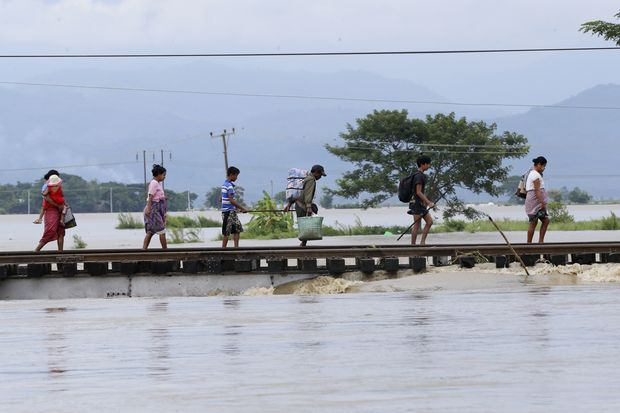 Residents walk at a flooded road due to ramping waters from Swar Chaung dam, at Yedashe city, Bago Region, near Naypyitaw, Myanmar, on Wednesday. (Photo by EPA-EFE)