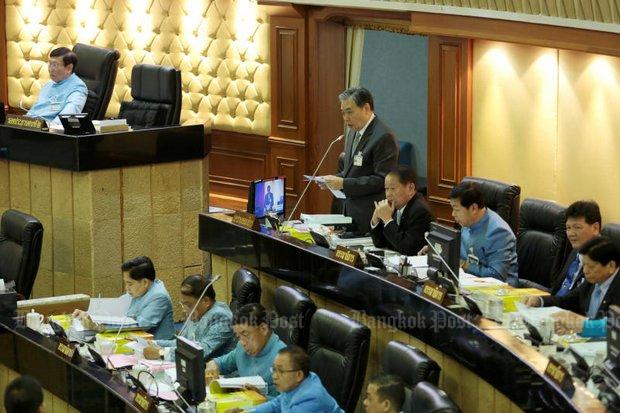 Finance Minister Apisak Tantivorawong (standing) shepherded the record 3.3 trillion baht budget bill through light scrutiny Thursday at the National Legislative Assembly. (Photo by Chanat Katanyu)