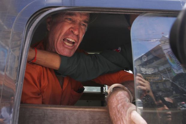 Australian filmmaker James Ricketson, 69, speaks from a prisoner truck during a lunch break at Phnom Penh Municipal Court, in Phnom Penh on Friday. He was later sentenced to six years in prison for espionage, for flying a drone over a political rally. (AP photo)