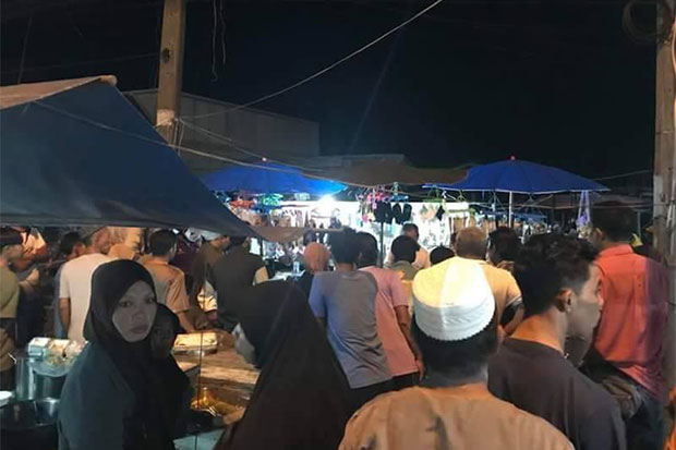 People gather in front of the stall at Ban Krue Sae community market in Pattani after gunmen killed a village defence volunteer and one woman, and wounded another woman, in full view of market-goers in Muang district on Thursday night. (Photo by Abdulloh Benjakat).
