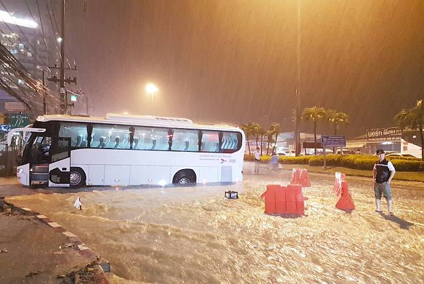 This tour coach became stuck in a large hole dug for the construction of a new drainage system on a road in Pattaya City on Monday night. The driver could not see it because the road was flooded. (Photo by Chaiyot Pupattanapong)