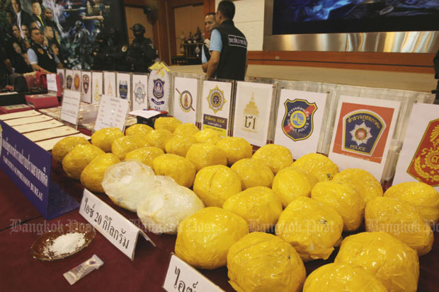 Packages of crystal methamphetamine wrapped in yellow tape are displayed by the Narcotics Suppression Bureau after operations targeting the