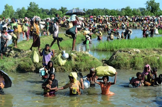 Rohingya refugees walk through a shallow canal after crossing the Naf River as they flee violence in Myanmar to reach Bangladesh in this photo taken in October of last year. (AFP photo)