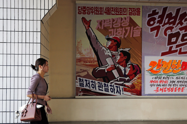 "A woman walks past propaganda posters at the Pyongyang Cosmetics Factory in Pyongyang on Saturday. The poster at left reads ""Let's thoroughly implement the decisions of the April meeting of the Central Committee of the Workers' Party of Korea."" (AP Photo)"