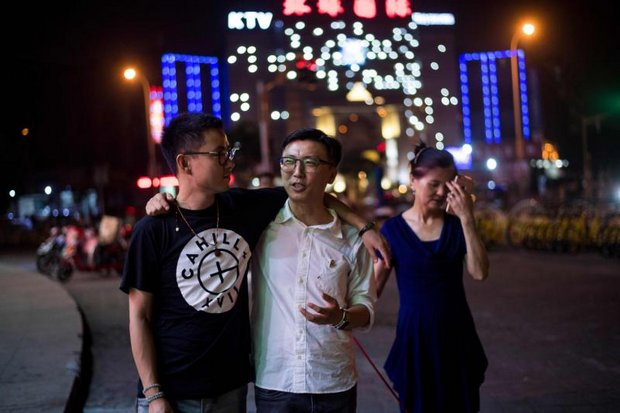 Duan Rongfen, left, and Li Tao, centre, walk their dog together with Li Tao's mother, He Fenglanm in Shanghai. (AFP photo)